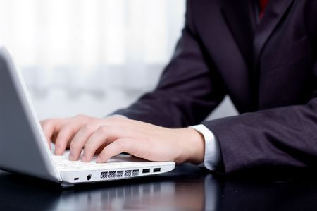 Businessman typing on a notebook (shallow DOF, hand in focus) Stock Photo