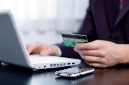 pagando: Hombre de negocios utilizando su tarjeta de cr�dito para una transacci�n en l�nea