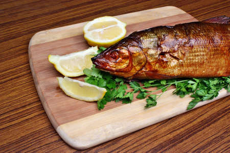 Fish smoked whitefish on a chopping board with lemon and parsley photo