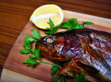whitefish: Fish smoked trout on a chopping board with lemon and parsley Stock Photo