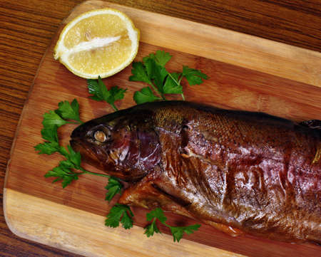 Fish smoked trout on a chopping board with lemon and parsley photo