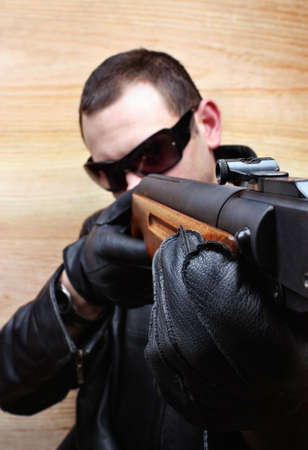 Menacing gangster mafia criminal shoots a gun Stock Photo - 26051211