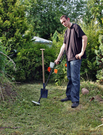 metal detector: Man exploration  treasures in the garden using a metal detector Stock Photo