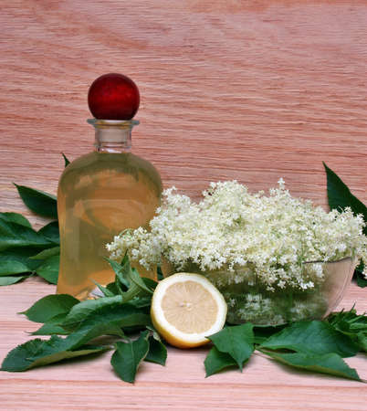 Syrup of flowers elderberry on wooden  photo
