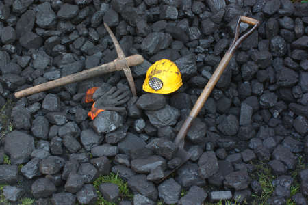 Shovel, pickaxe, gloves, mining helmet in the background heap of coal
