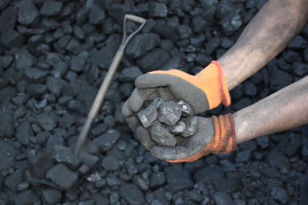 Coal miner holding a stone