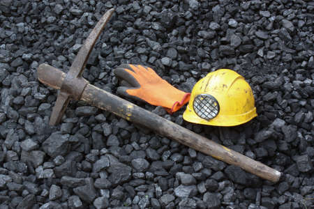 Pickaxe, gloves, mining helmet in the background heap of coal Stock Photo