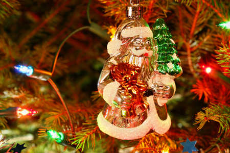 Santa Claus ornament hanging on the Christmas tree photo
