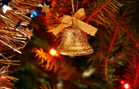 Gold bell ornament hanging on the Christmas tree photo