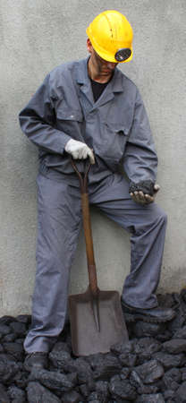 coal miner: Holding a stone coal miner with a shovel mining Stock Photo