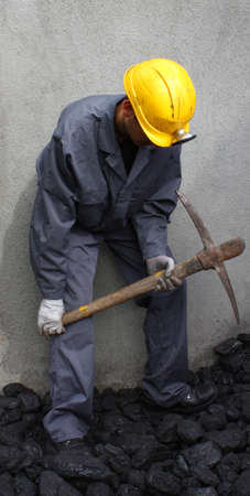 pickaxe: Miner using a pickaxe to break up the mining of coal