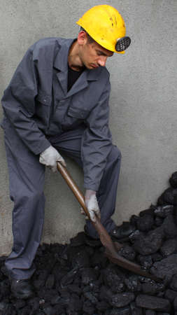 coal miner: Working with loading coal miner in work clothes Stock Photo