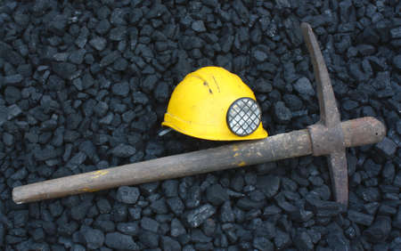 Pickaxe, mining helmet in the background heap of coal