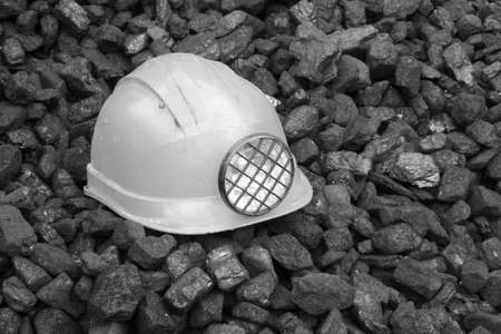 Mining helmet in the background heap of coal, black and white photo Stock Photo