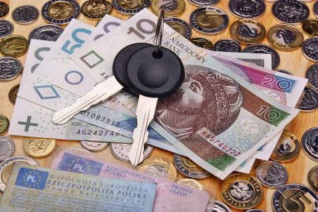 Los documentos de las llaves del coche y monedas de dinero sobre la mesa Foto de archivo