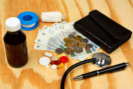 health care costs: Medical pills and stethoscope in polish money background as a symbol of health care costs