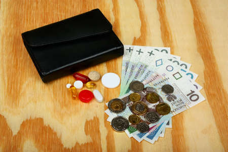 hospital expenses: Polish money and wallet on wooden background