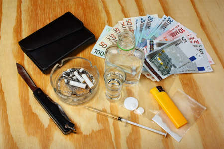 drug deals: Cigarettes, drugs, tablets, boosters, syringe, vodka and money euro are wooden table