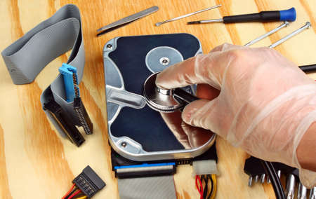 hard drive crash: Computer hdd and hand with stethoscope on a wooden table Stock Photo