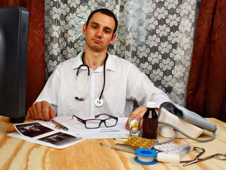 doctor with pills: Happy male doctor looking at camera in medical office Stock Photo