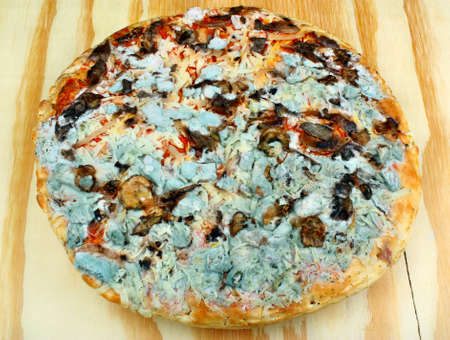 poisoning: Old moldy pizza on a wooden table. Food poisoning