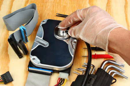 Hand with gloves repairs hard drive data recovery concept