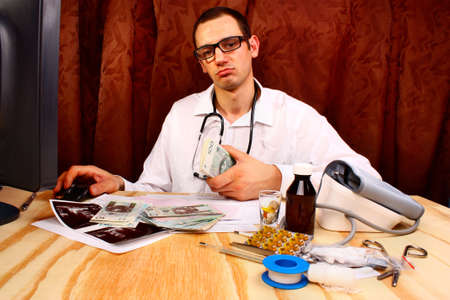doctor holding money: A handsome doctor holding polish money in doctors office