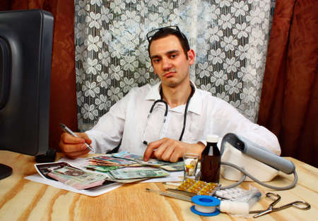 doctor money: A handsome doctor have euro and polish money in doctors office Stock Photo