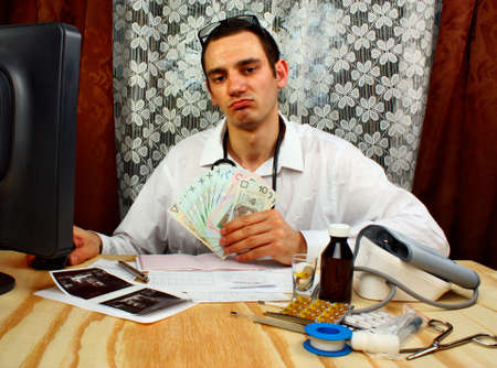 doctor holding money: Young doctor holding polish money in doctors office Stock Photo
