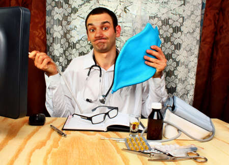 proctologist: Doctor proctologist  is wearing white medicine uniform and holding blue enema in hands