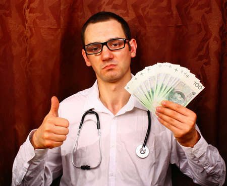 doctor money: Surgeon doctor in white uniform showing thumbs up symbol and hold polish money