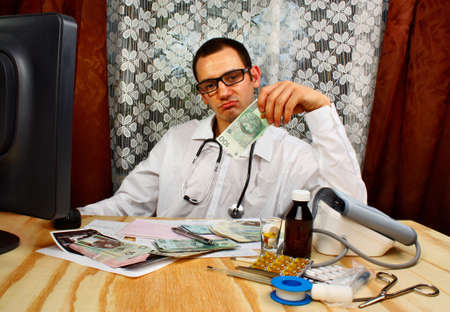 doctor money: Young doctor holding polish money in doctors office Stock Photo
