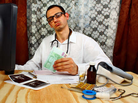 doctor holding money: A handsome doctor holding euro money in doctors office