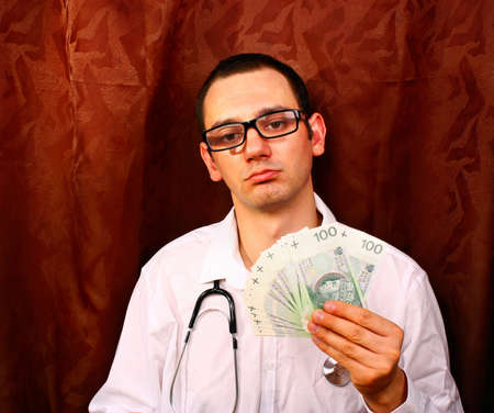 doctor holding money: Young doctor holding euro money in doctors office Stock Photo