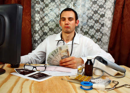 doctor money: A handsome doctor holding polish money in doctors office