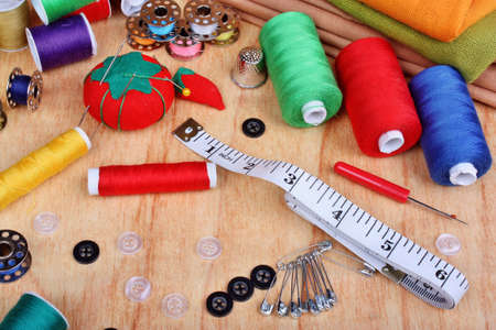 Sewing items: buttons, colorful fabrics, material, measuring tape, bobbins, buttons, cloth, safety pins, needles, pincushion, thimble, spools of thread