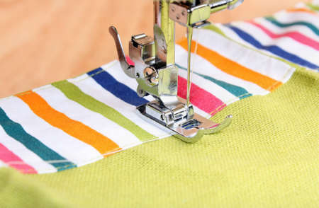 stitchwork: Sewing machine and item of clothing material  background threads