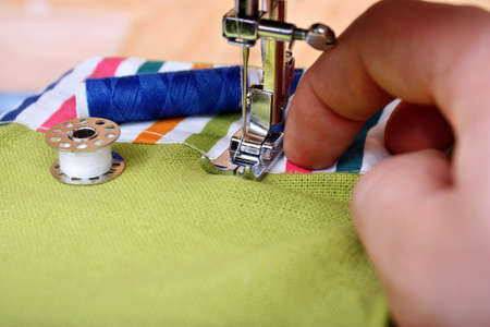 stitchwork: Hand sewing on a machine and item of clothing material