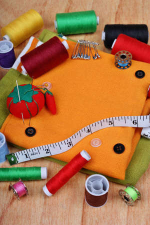 Background vertical with sewing items: buttons, colorful fabrics, material, measuring tape, bobbins, buttons, cloth, safety pins, needles, pincushion, thimble, spools of thread