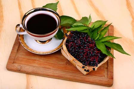 Fresh cup tea fruit elderberry on the wooden table