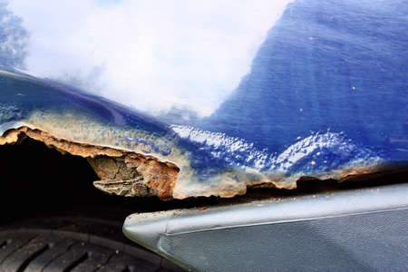 iron oxide: Heavily corroded rusty wheel arches in a blue car