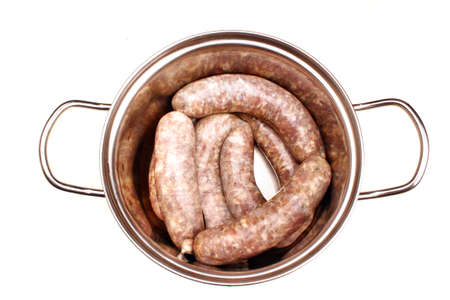 Raw meat sausages isolated in a pot ready for cooking on white background Stock Photo