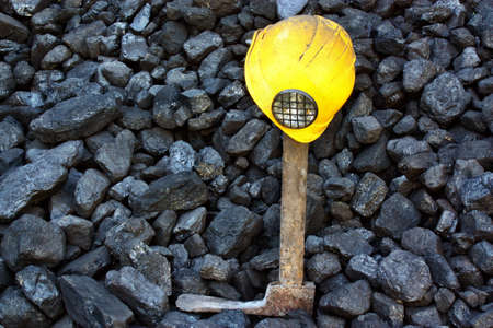 pickaxe: Pickaxe, mining helmet in the background heap of coal