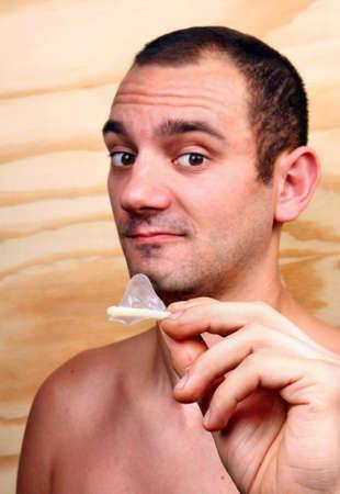 condones: Chico guapo joven muestra y mantiene un condón en la mano