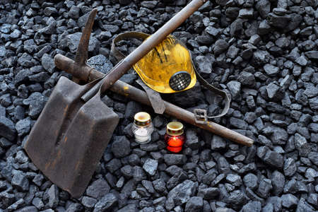 Vigil light, candle with the minerals belongings (helmet, pickaxe, shovel, belt) after the fatal accident in the mine Stock Photo