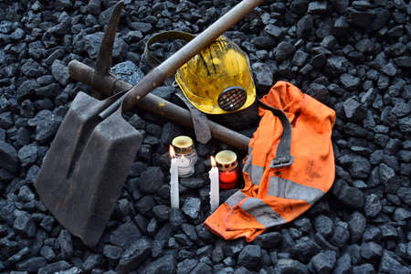 Vigil light, candle with the minerals belongings (helmet, pickaxe, shovel, vest, belt) after the fatal accident in the mine
