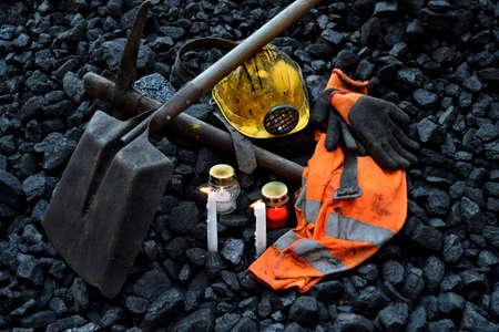 Vigil light, candle with the miner belongings (helmet, gloves, pickaxe, shovel, vest, belt) after the fatal accident in the mine