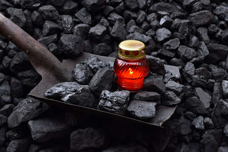 Vigil light, candle with the miner belongings (pickaxe, shovel) after the fatal accident in the mine