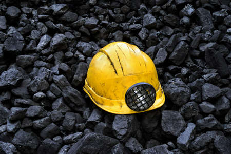 Yellow miners safety helmet on top of the coal mining