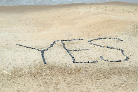Yes concept word written on sand beach with stones mean positive changes in the life, job
